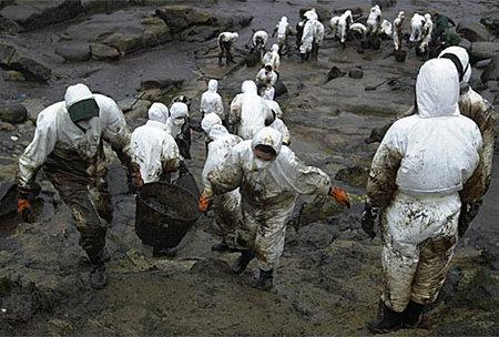 Imagen de voluntarios limpiando petróleo en las costas gallegas en 2002